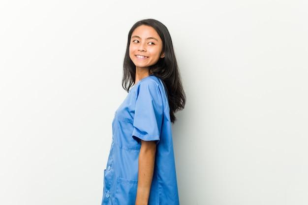若いアジアの看護師の女性は笑みを浮かべて、陽気で快適な脇に見えます。