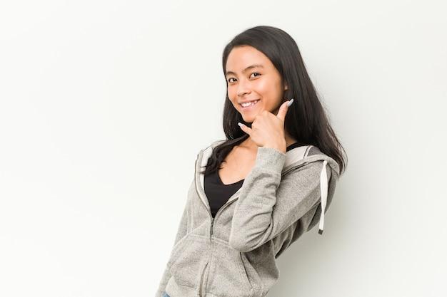 Женщина молодого фитнеса китайская показывая жест звонка мобильного телефона с пальцами.