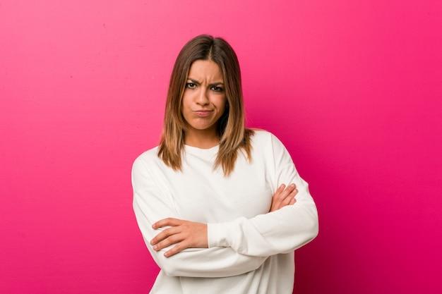皮肉な表情でカメラで見て不幸な壁に若い本物のカリスマ的な実在の女性。