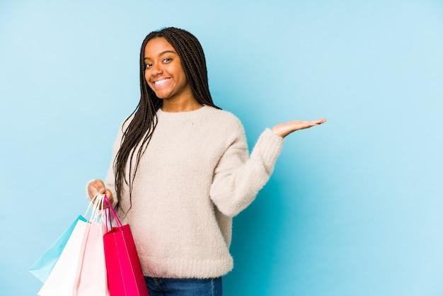 Молодая афро-американская женщина держа хозяйственную сумку показывая космос экземпляра на ладони и держа другую руку на талии.