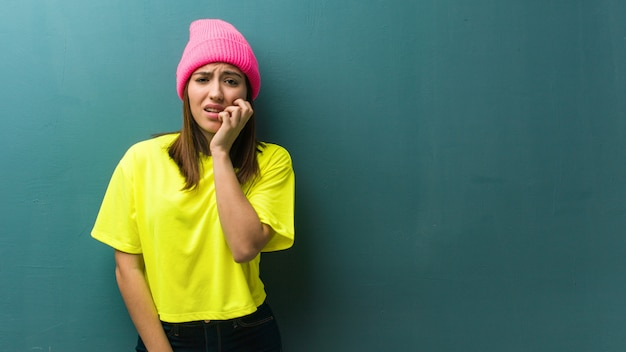 爪をかむ若い現代の女性、神経質で非常に心配
