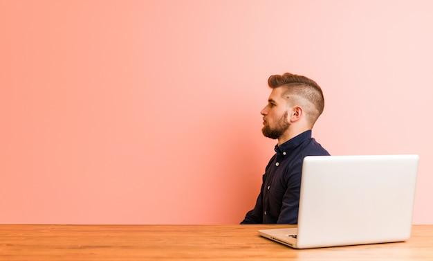 若い男が彼のラップトップを左に見つめて作業、横向きのポーズ。