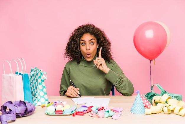 Молодая афро-американская женщина планируя день рождения имея некоторую отличную идею