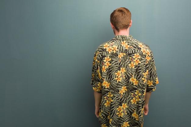 Рыжий молодой человек в экзотической летней одежде сзади, оглядываясь назад