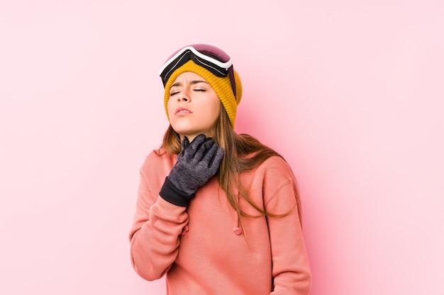 スキー服を着た若い白人女性は、ウイルスや感染症のために喉の痛みに苦しんでいます。