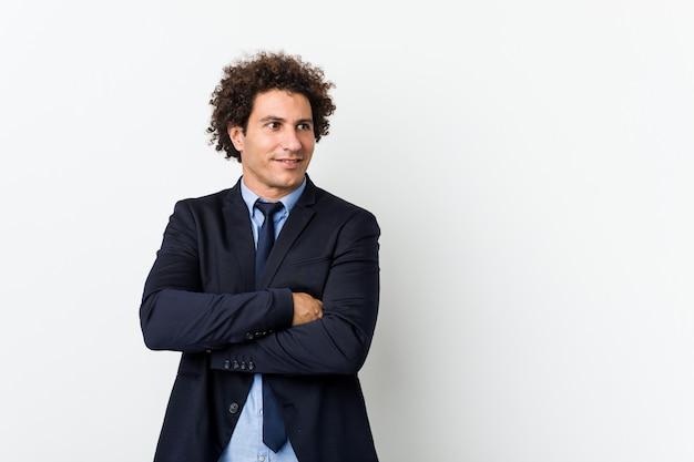 組んだ腕に自信を持って笑顔白い背景に対して若いビジネス中の男。