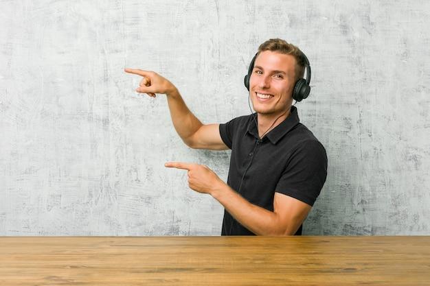 ヘッドフォンで音楽を聴く若い白人男は人差し指で離れて指している興奮しています。