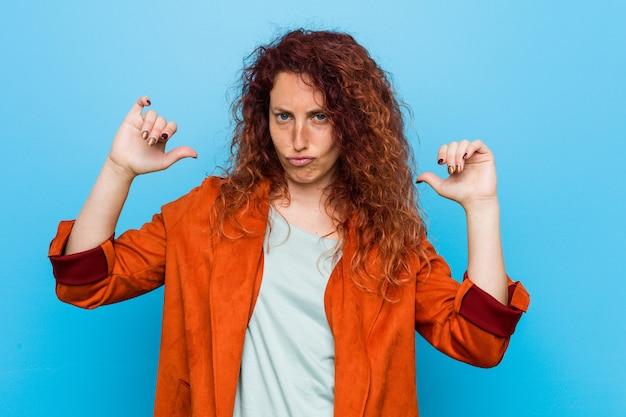 若い赤毛のエレガントな女性は誇りに思って、自信を持って、次の例です。