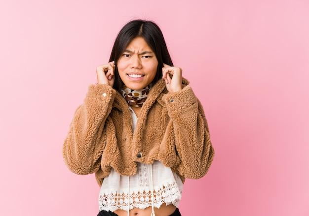 若いアジアの女性の手で耳を覆っています。