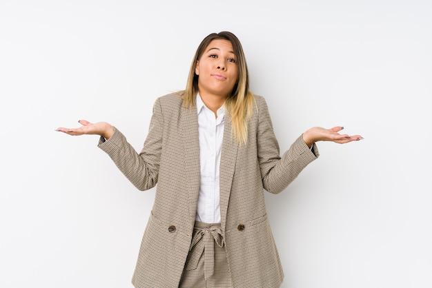 若い白人のビジネス女性が疑い、ジェスチャーの質問で肩をすくめ。