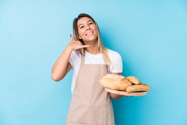 Молодая кавказская женщина хлебопека показывая жест звонка мобильного телефона с пальцами.