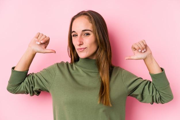 ポーズをとる若い白人女性は誇りと自信を持っていると感じています。