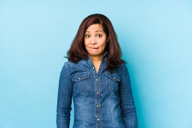 混乱している青色の背景に中年のラテン女性は、疑わしく不安を感じています。