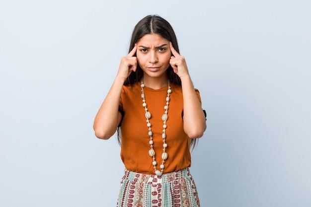 Молодая арабская женщина сосредоточена на задаче, держа указательные пальцы указывая головой.