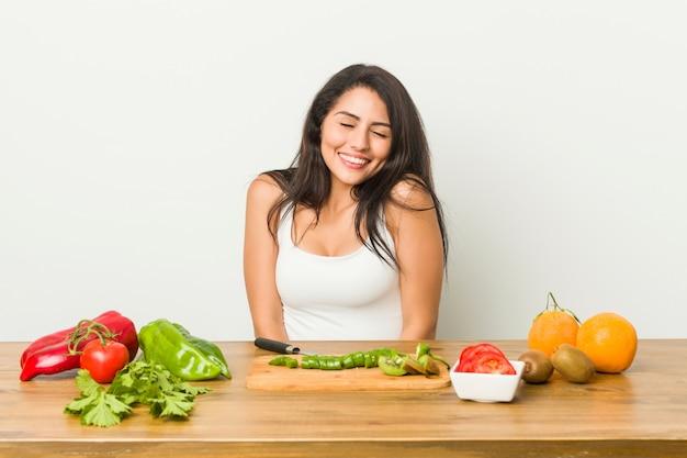 Молодая соблазнительная женщина, готовящая здоровую еду, смеется и закрывает глаза, чувствует себя расслабленной и счастливой.