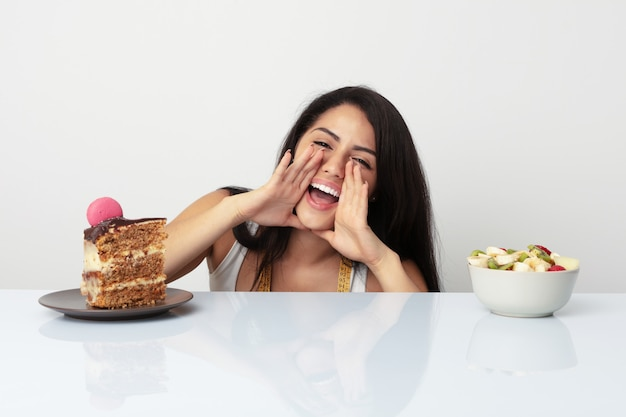 Молодая испанская женщина, выбор между торт или фрукты кричали возбужденных на фронт.