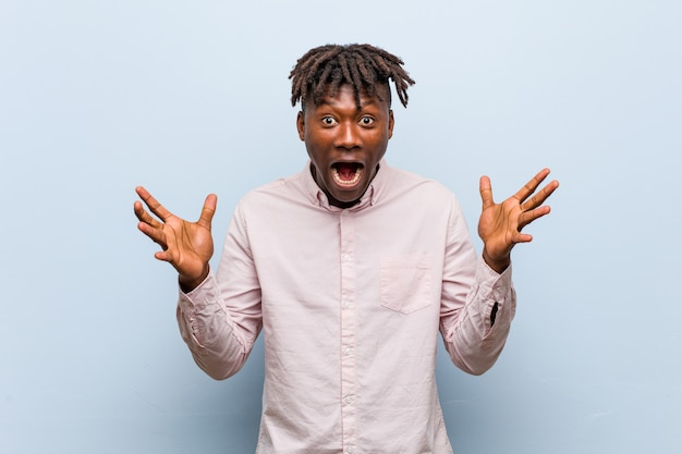Молодой бизнес африканский черный человек празднует победу или успех