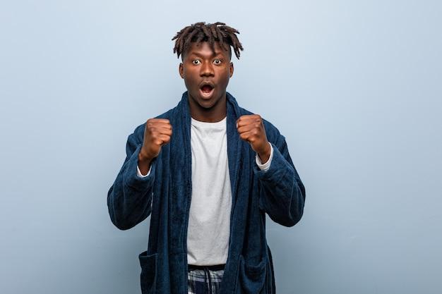 Молодой африканский темнокожий мужчина, носящий пижаму, приветствующую беззаботный и взволнованный. концепция победы.