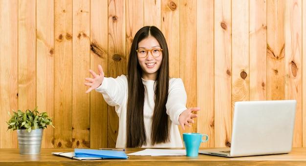 Молодая китаянка, изучая на своем столе чувствует себя уверенно, давая обнять камеру.
