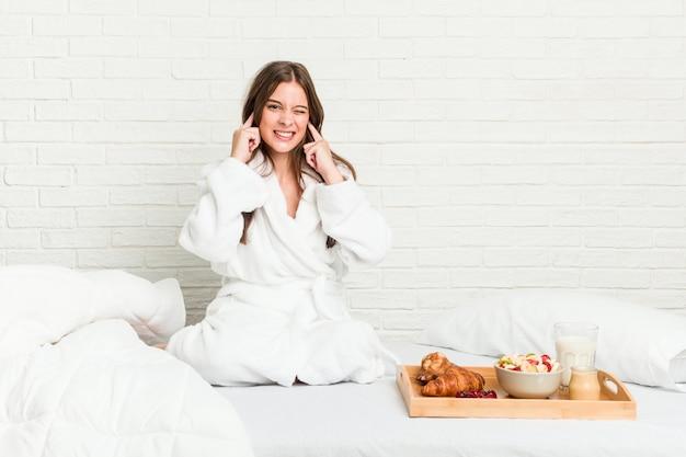 Молодая кавказская женщина на кровати покрывая уши руками.