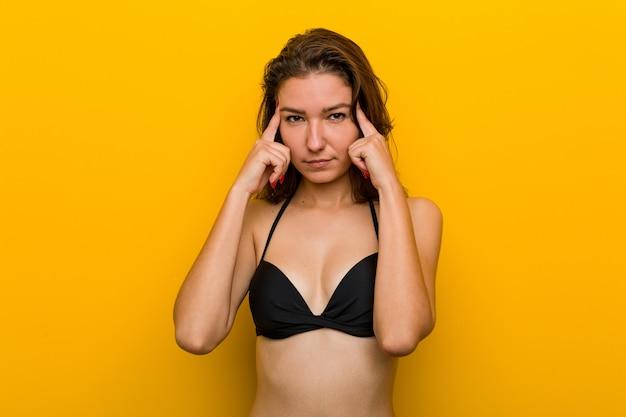 ビキニを着た若いヨーロッパ人女性は、人差し指を頭に向けたまま、タスクに集中しました。