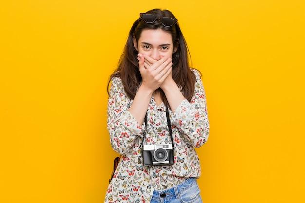 若いブルネットの旅行者の女性は手で口を覆ってショックを受けた。