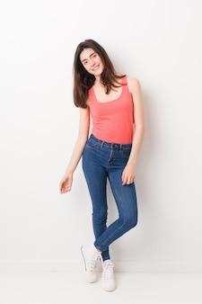白い壁に立っている若い白人女性