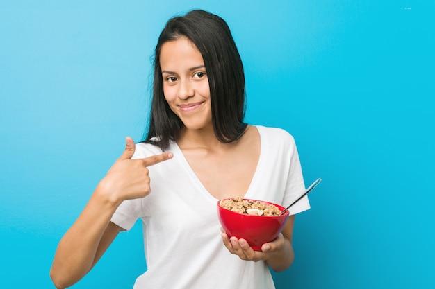 Молодая испанская женщина, держащая миску зерновых, указывая пальцем на вас, как будто приглашая подойти ближе.