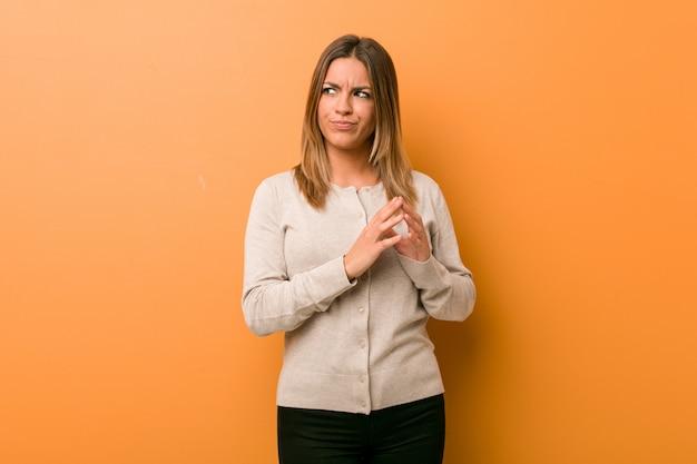 アイデアを設定する計画を考えて壁に向かって若い本物のカリスマ的な実在の女性。