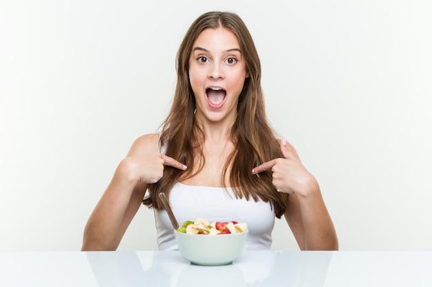 フルーツボウルを食べる若い白人女性は自分自身を指して驚いて