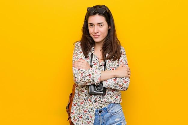 自信を持って、決意を持って腕を組んでいる若いブルネット旅行者の女性。