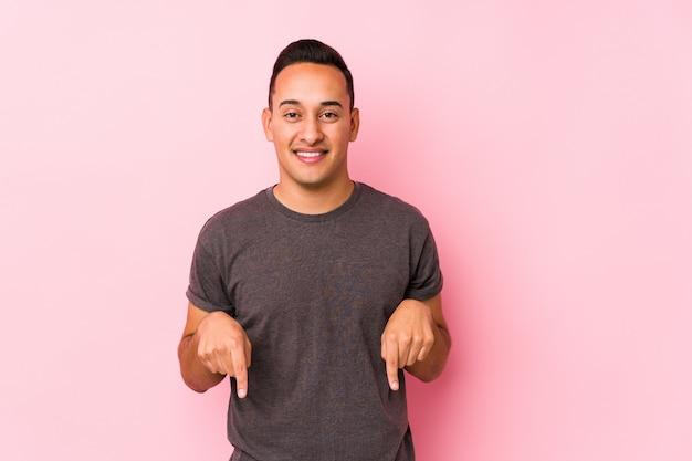Молодой латинский мужчина позирует в розовой стене с пальцами, положительное чувство.