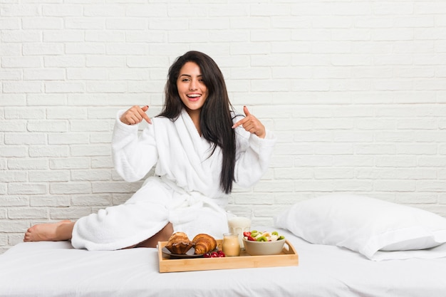 Молодая соблазнительная женщина, принимая завтрак на кровати указывает пальцами вниз, позитивные чувства.
