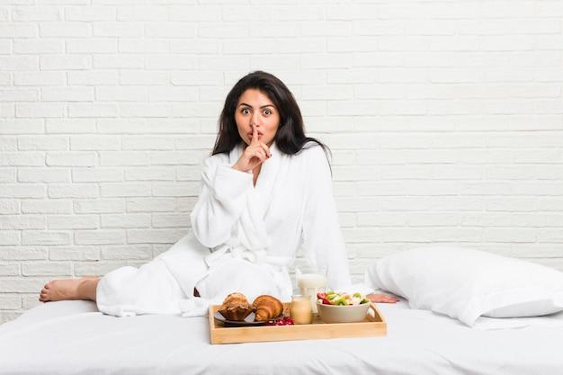 Молодая соблазнительная женщина, принимая завтрак на кровати, сохраняя в тайне или прося молчания.