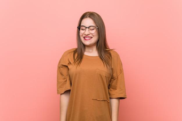 Молодой студент женщина очках смеется и закрывает глаза, чувствует себя расслабленным и счастливым.