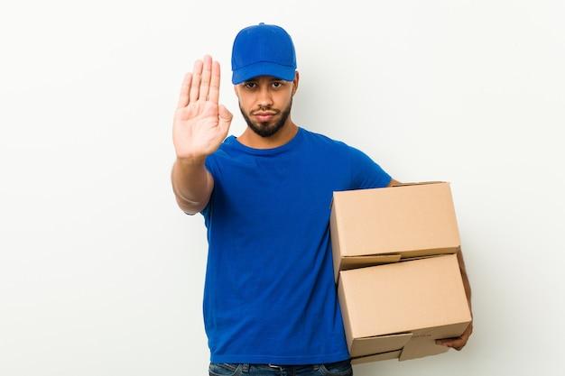 Молодой южно-азиатский работник доставляющий покупки на дом стоя при протягиванная рука показывая знак стопа, предотвращая вас.