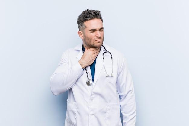 若いハンサムな医者の男は、ウイルスや感染症のため喉の痛みに苦しんでいます。