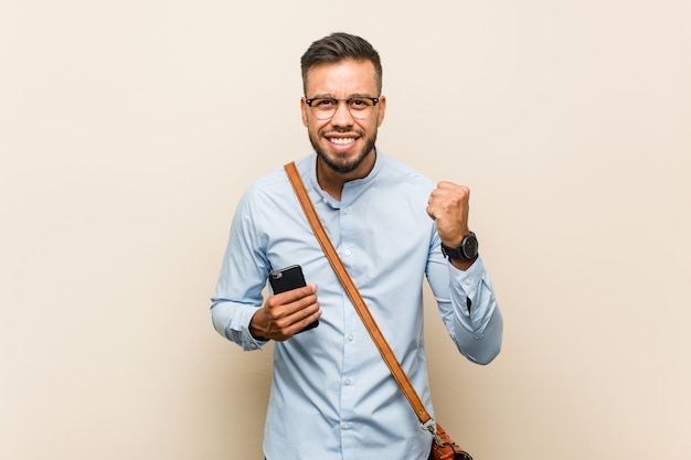 Бизнесмен молодой смешанной гонки азиатский держа веселить телефона беспечальный и возбужденный. концепция победы.