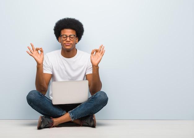Молодой черный человек, сидя на полу с ноутбуком, выполняя йогу
