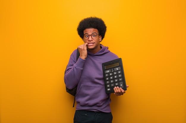 若いアフリカ系アメリカ人学生の男、爪をかむ、神経質で非常に不安な電卓を保持