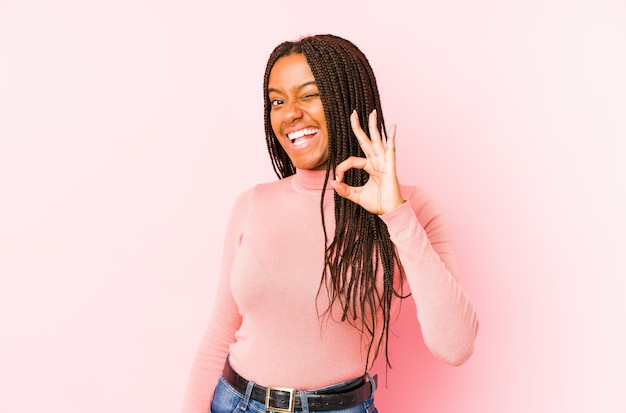 ピンクの壁に分離された若いアフリカ系アメリカ人女性は目をまばたきし、手でいいジェスチャーを保持します。
