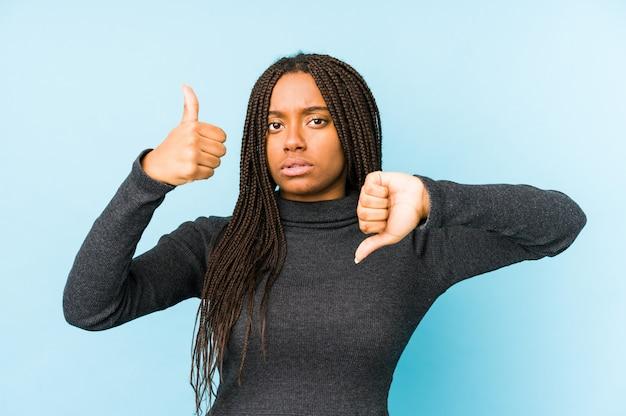 親指と親指を示す青い壁に分離された若いアフリカ系アメリカ人女性、難しい選択コンセプト