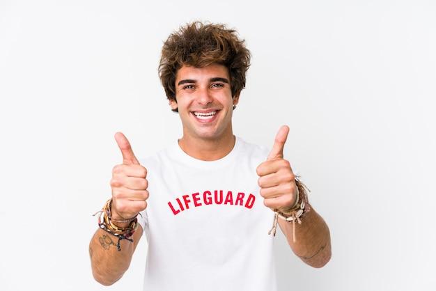 若い白人のライフガードは、親指で隔離された白い壁に対してガードし、何かについて応援し、概念をサポートします。