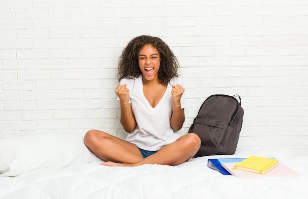 屈託のない、興奮して応援ベッドの上の若いアフリカ系アメリカ人学生女性。勝利のコンセプト。