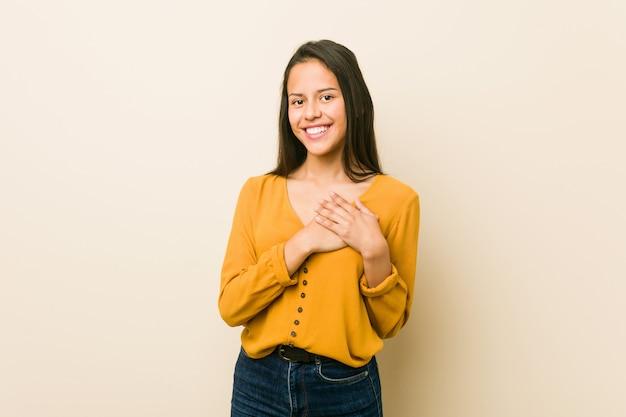 Молодая латиноамериканка на фоне бежевой стены имеет дружелюбное выражение, прижимая ладонь к груди. концепция любви