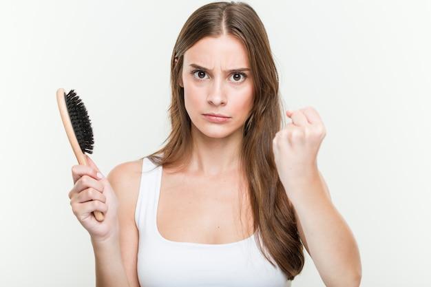 Молодая кавказская женщина держа щетку волос показывая кулак к с агрессивным выражением лица.