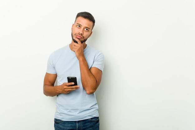 電話を保持している若い混血アジア人が何かについてリラックスした思考