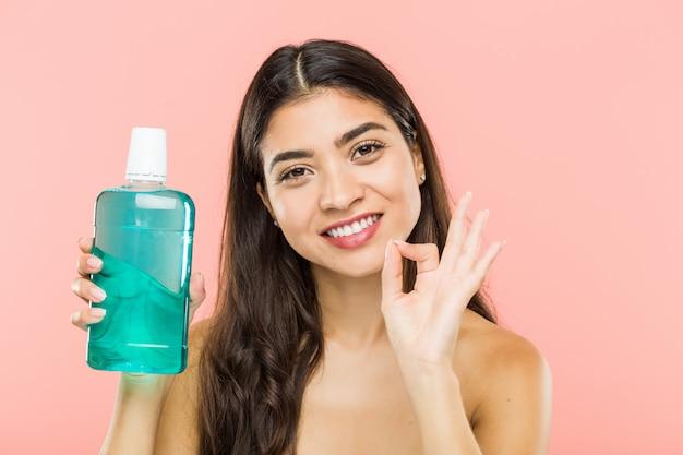 Молодая женщина, держа бутылку для полоскания рта, веселый и уверенный, показывая ок жест.