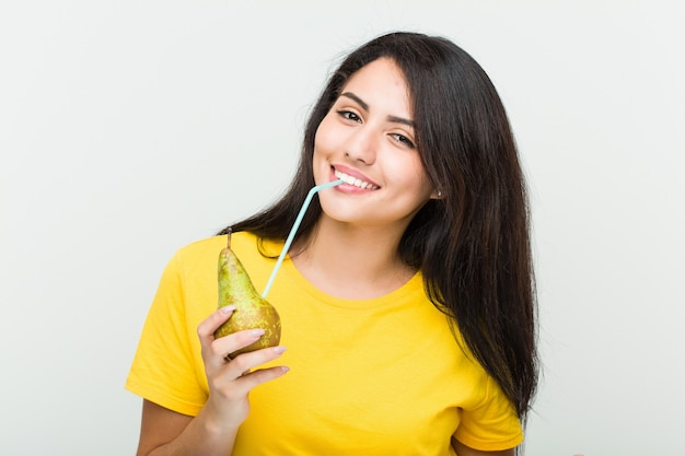 ストローで梨ジュースを飲む若い女性
