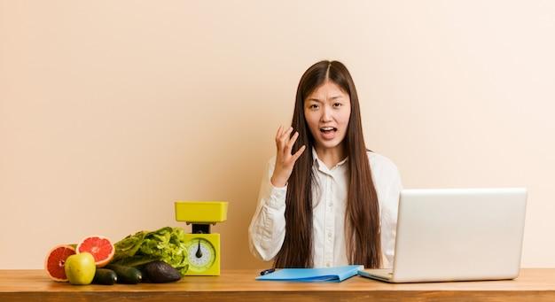 怒りで叫んでいる彼女のラップトップで働く若い栄養士中国の女性。